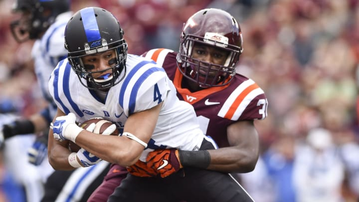 BLACKSBURG, VA – OCTOBER 24: Wide receiver Johnell Barnes #4 of the Duke Blue Devils is wrapped up after his reception by cornerback Brandon Facyson #31 of the Virginia Tech Hokies in the first half at Lane Stadium on October 24, 2015 in Blacksburg, Virginia. (Photo by Michael Shroyer/Getty Images)