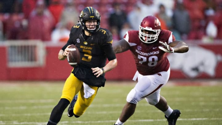 FAYETTEVILLE, AR - NOVEMBER 27: Drew Lock #3 of the Missouri Tigers runs the ball after pressure from Bijhon Jackson #78 of the Arkansas Razorbacks at Razorback Stadium Stadium on November 27, 2015 in Fayetteville, Arkansas. The Razorbacks defeated the Tigers 28-3. (Photo by Wesley Hitt/Getty Images)