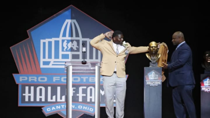 CANTON, OH - AUGUST 05: LaDainian Tomlinson reacts as he and presenter Lorenzo Neal unveil Tomlinson's bust during the Pro Football Hall of Fame Enshrinement Ceremony at Tom Benson Hall of Fame Stadium on August 5, 2017 in Canton, Ohio. (Photo by Joe Robbins/Getty Images)