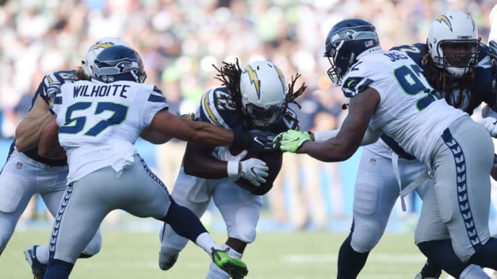 CARSON, CA - AUGUST 13: Running back Melvin Gordon #28 of the Los Angeles Chargers rushes as he is tackled by Mike Morgan #57 and Nazair Jones #92 of the Seattle Seahawks during a pre season football game at StubHub Center August 13, 2017, in Carson, California. (Photo by Kevork Djansezian/Getty Images)