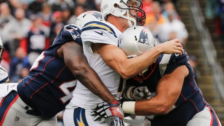 FOXBORO, MA - OCTOBER 29: Philip Rivers #17 of the Los Angeles Chargers is tackled by David Harris #45 and Lawrence Guy #93 of the New England Patriots during the fourth quarter of a game at Gillette Stadium on October 29, 2017 in Foxboro, Massachusetts. (Photo by Jim Rogash/Getty Images)