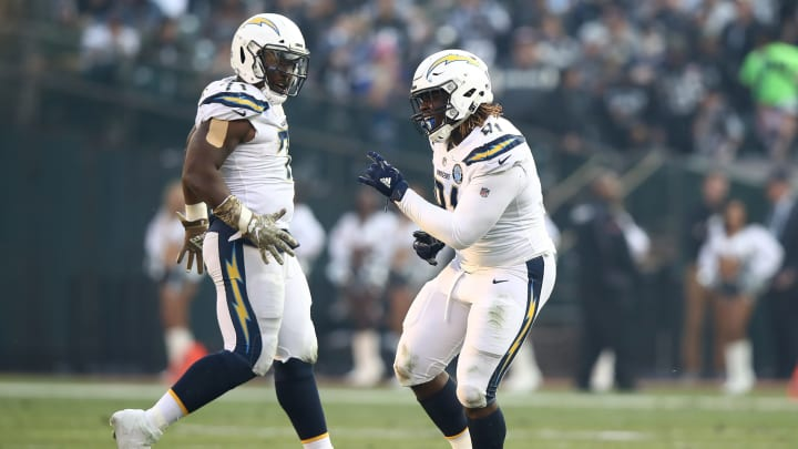 OAKLAND, CA – NOVEMBER 11: Damion Square #71 and Justin Jones #91 of the Los Angeles Chargers celebrate after a play against the Oakland Raiders during their NFL game at Oakland-Alameda County Coliseum on November 11, 2018 in Oakland, California. (Photo by Ezra Shaw/Getty Images)