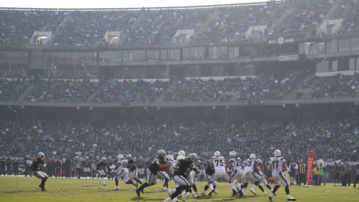 OAKLAND, CA - NOVEMBER 11: A smokey haze is seen as Philip Rivers #17 of the Los Angeles Chargers drops back to pass against the Oakland Raiders during their NFL game at Oakland-Alameda County Coliseum on November 11, 2018 in Oakland, California. An Air Quality Advisory was issued due to heavy wildfire smoke in parts of the Bay Area from the Camp Fire in Butte County. (Photo by Ezra Shaw/Getty Images)