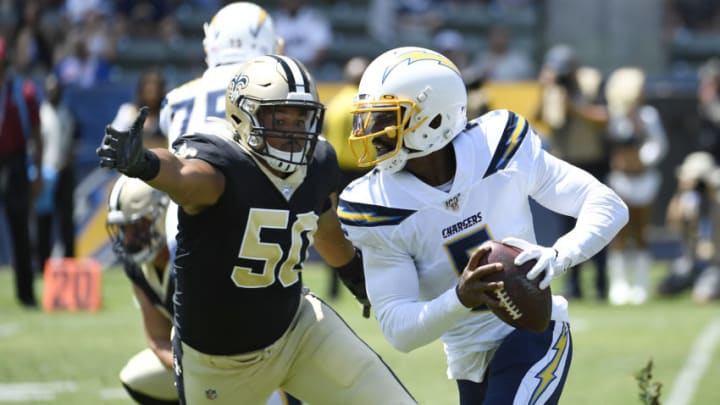 CARSON, CA - AUGUST 18: Quarterback Tyrod Taylor #5 of the Los Angeles Chargers eludes a tackle by Wes Horton #50 of the New Orleans Saints during the first half of their pre-seaon football game at Dignity Health Sports Park on August 18, 2019 in Carson, California. (Photo by Kevork Djansezian/Getty Images)