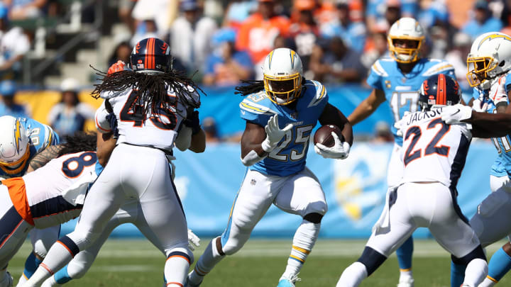 CARSON, CALIFORNIA – OCTOBER 06: Melvin Gordon #25 of the Los Angeles Chargers runs the ball as Kareem Jackson #22 and Alexander Johnson #45 of the Denver Broncos defend during the first half of a game at Dignity Health Sports Park on October 06, 2019 in Carson, California. (Photo by Sean M. Haffey/Getty Images)