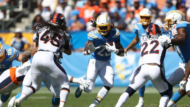CARSON, CALIFORNIA - OCTOBER 06: Melvin Gordon #25 of the Los Angeles Chargers runs the ball as Kareem Jackson #22 and Alexander Johnson #45 of the Denver Broncos defend during the first half of a game at Dignity Health Sports Park on October 06, 2019 in Carson, California. (Photo by Sean M. Haffey/Getty Images)