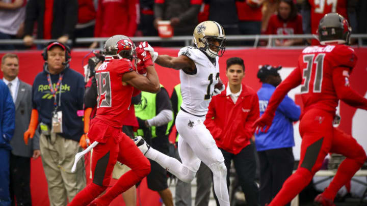 TAMPA, FLORIDA - NOVEMBER 17: Michael Thomas #13 of the New Orleans Saints stiff-arms Andrew Adams #39 of the Tampa Bay Buccaneers on a 41-yard catch and run during the third quarter of the game against the Tampa Bay Buccaneers on November 17, 2019 at Raymond James Stadium in Tampa, Florida. (Photo by Will Vragovic/Getty Images)