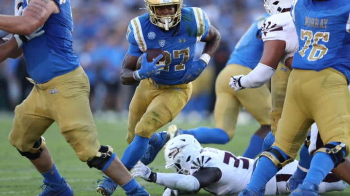 LOS ANGELES, CALIFORNIA - OCTOBER 26: Joshua Kelley #27 of the UCLA Bruins runs with the ball past Jermayne Lole #90 of the Arizona State Sun Devils for short yardage during the first half of a game on October 26, 2019 in Los Angeles, California. (Photo by Sean M. Haffey/Getty Images)