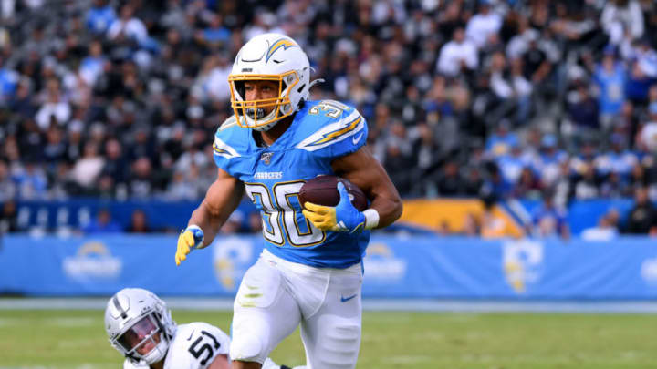 CARSON, CALIFORNIA - DECEMBER 22: Austin Ekeler #30 of the Los Angeles Chargers runs after breaking a tackle from Will Compton #51 of the Oakland Raiders during the second quarter at Dignity Health Sports Park on December 22, 2019 in Carson, California. (Photo by Harry How/Getty Images)
