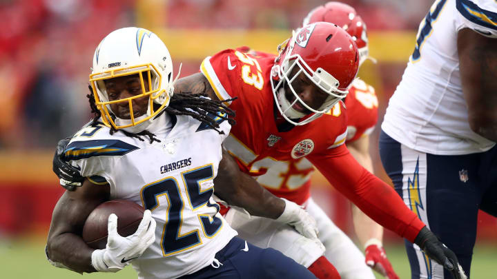 KANSAS CITY, MISSOURI – DECEMBER 29: Running back Melvin Gordon #25 of the Los Angeles Chargers carries the ball as inside linebacker Anthony Hitchens #53 of the Kansas City Chiefs defends at Arrowhead Stadium on December 29, 2019 in Kansas City, Missouri. (Photo by Jamie Squire/Getty Images)