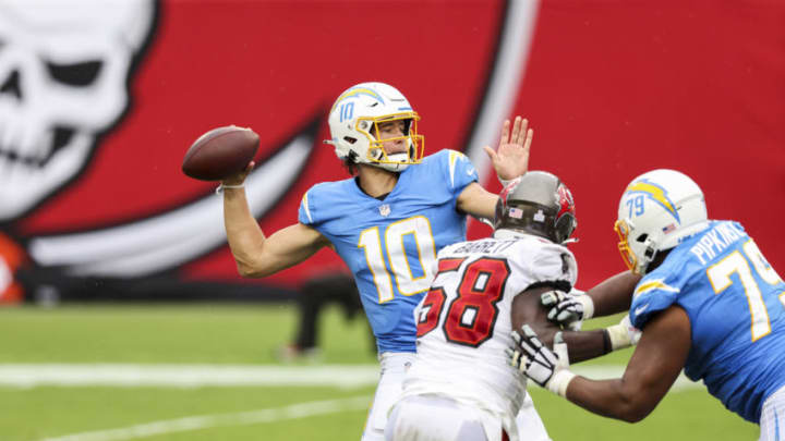 TAMPA, FLORIDA - OCTOBER 04: Justin Herbert #10 of the Los Angeles Chargers looks to pass against Shaquil Barrett #58 of the Tampa Bay Buccaneers during the first half of a game at Raymond James Stadium on October 04, 2020 in Tampa, Florida. (Photo by James Gilbert/Getty Images)