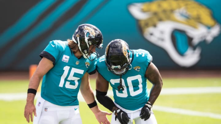 JACKSONVILLE, FLORIDA - OCTOBER 18: Gardner Minshew #15 of the Jacksonville Jaguars and James Robinson #30 warm up before the start of a game against the Detroit Lions at TIAA Bank Field on October 18, 2020 in Jacksonville, Florida. (Photo by James Gilbert/Getty Images)