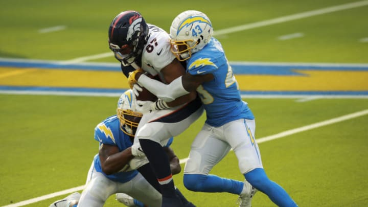 INGLEWOOD, CALIFORNIA - DECEMBER 27: Denzel Perryman #52 and Michael Davis #43 of the Los Angeles Chargers tackle Noah Fant #87 of the Denver Broncos during the first quarter at SoFi Stadium on December 27, 2020 in Inglewood, California. (Photo by Joe Scarnici/Getty Images)