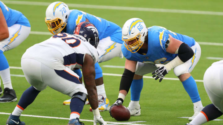 INGLEWOOD, CALIFORNIA - DECEMBER 27: Dan Feeney #66 of the Los Angeles Chargers and DeShawn Williams #90 of the Denver Broncos prepare for the snap in the third quarter at SoFi Stadium on December 27, 2020 in Inglewood, California. (Photo by Joe Scarnici/Getty Images)
