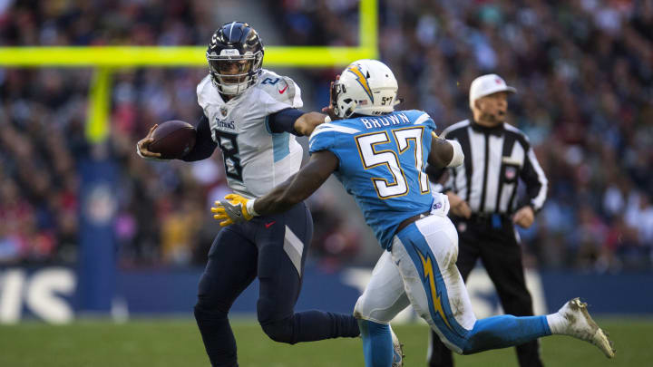 LONDON, ENGLAND – OCTOBER 21: Marcus Mariota (8) of the Tennessee Titans holds off Jatavis Brown (57) of the Los Angeles Chargers during the Tennessee Titans against the Los Angeles Chargers at Wembley Stadium on October 21, 2018 in London, England. (Photo by Justin Setterfield/Getty Images)