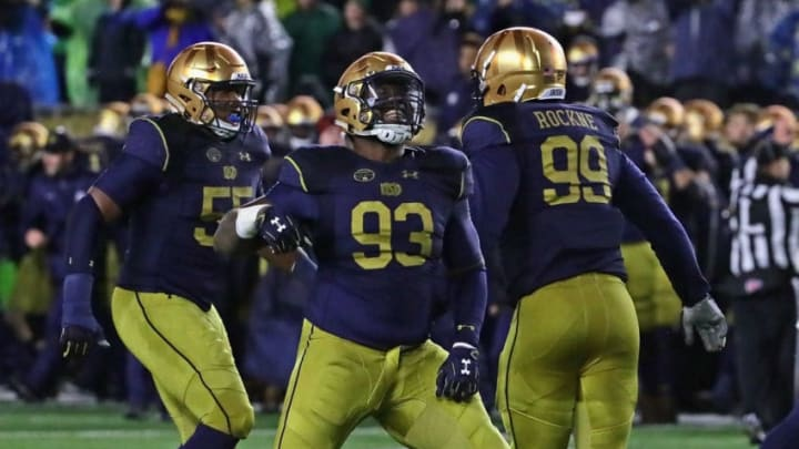 SOUTH BEND, IN - NOVEMBER 18: (L-R) Jonathan Bonner #55, Jay Hayes #93 and Jerry Tillery #99 of the Notre Dame Fighting Irish celebrate a defensive stop on 4th down against the Navy Midshipmen at Notre Dame Stadium on November 18, 2017 in South Bend, Indiana. Notre Dame defeated Navy 24-17. (Photo by Jonathan Daniel/Getty Images)