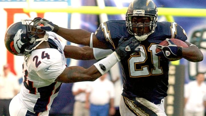 San Diego Charger LaDainian Tomlinson (R) fends off Denver Bronco cornerback Deltha O'Neal as he drives for yardage in the second quarter, setting up his third touchdown 01 December, 2002, at San Diego Qualcomm Stadium. AFP PHOTO/TOM KURTZ (Photo by TOM KURTZ / AFP) (Photo credit should read TOM KURTZ/AFP via Getty Images)