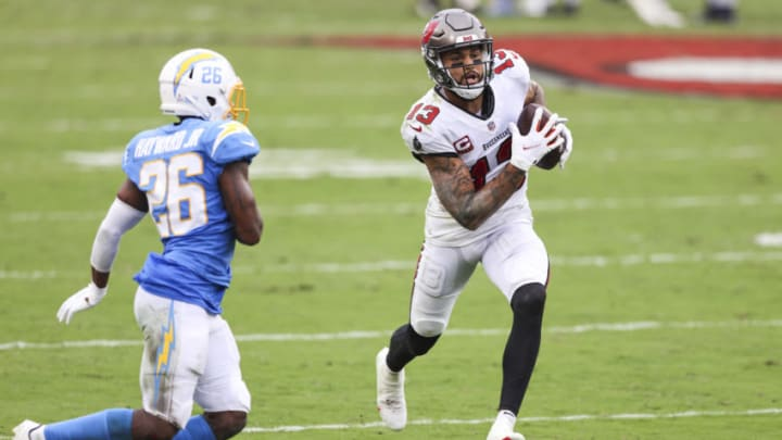 TAMPA, FLORIDA - OCTOBER 04: Mike Evans #13 of the Tampa Bay Buccaneers runs for yardage after a catch against Casey Hayward #26 of the Los Angeles Chargers during the fourth quarter of a game at Raymond James Stadium on October 04, 2020 in Tampa, Florida. (Photo by James Gilbert/Getty Images)
