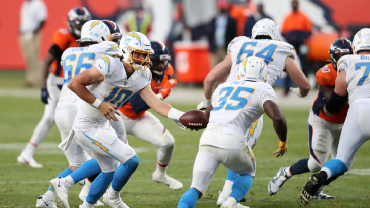 DENVER, COLORADO - NOVEMBER 01: Quarterback Justin Herbert #10 of the Los Angeles Chargers hands the ball off to teammate Troymaine Pope #35 as they take on the Denver Broncos in the fourth quarter of the game at Empower Field At Mile High on November 01, 2020 in Denver, Colorado. (Photo by Matthew Stockman/Getty Images)
