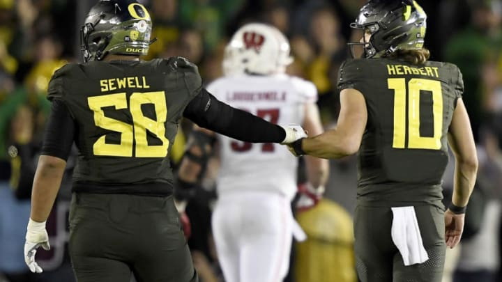 PASADENA, CALIFORNIA - JANUARY 01: Penei Sewell #58 and Justin Herbert #10 of the Oregon Ducks celebrate after defeating the Wisconsin Badgers in the Rose Bowl game presented by Northwestern Mutual at Rose Bowl on January 01, 2020 in Pasadena, California. (Photo by Kevork Djansezian/Getty Images)