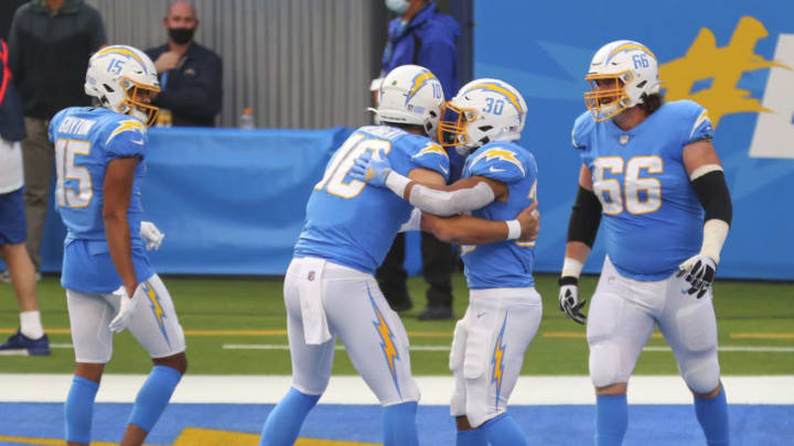 INGLEWOOD, CALIFORNIA - DECEMBER 27: Justin Herbert #10 of the Los Angeles Chargers congratulates Austin Ekeler #30 after a touchdown during the second quarter against the Denver Broncos at SoFi Stadium on December 27, 2020 in Inglewood, California. (Photo by Joe Scarnici/Getty Images)