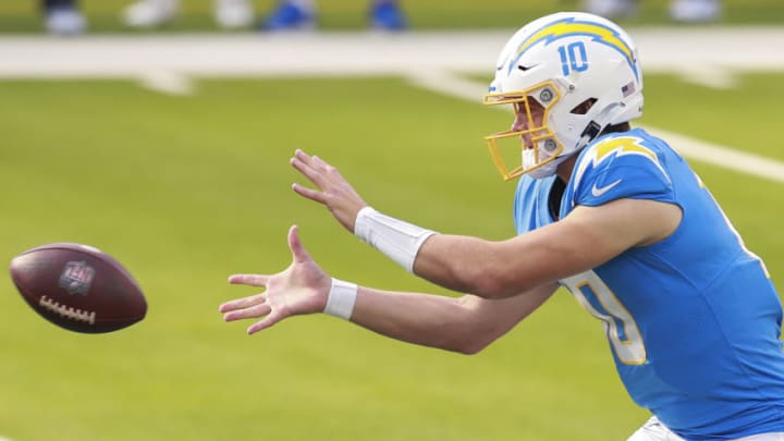 INGLEWOOD, CALIFORNIA - DECEMBER 27: Justin Herbert #10 of the Los Angeles Chargers takes the snap during the first quarter against the Denver Broncos at SoFi Stadium on December 27, 2020 in Inglewood, California. (Photo by Joe Scarnici/Getty Images)