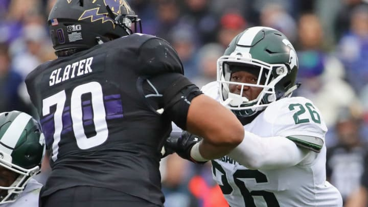 EVANSTON, IL - OCTOBER 28: Brandon Randle #26 of the Michigan State Spartans rushes against Rashawn Slater #70 of the Northwestern Wildcats at Ryan Field on October 28, 2017 in Evanston, Illinois. Northwestern defeated Michigan State 39-31 in triple overtime. (Photo by Jonathan Daniel/Getty Images)