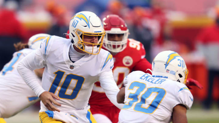 KANSAS CITY, MISSOURI - JANUARY 03: Quarterback Justin Herbert #10 of the Los Angeles Chargers hands off to Austin Ekeler #30 during the 1st half of the game against the Kansas City Chiefs at Arrowhead Stadium on January 03, 2021 in Kansas City, Missouri. (Photo by Jamie Squire/Getty Images)