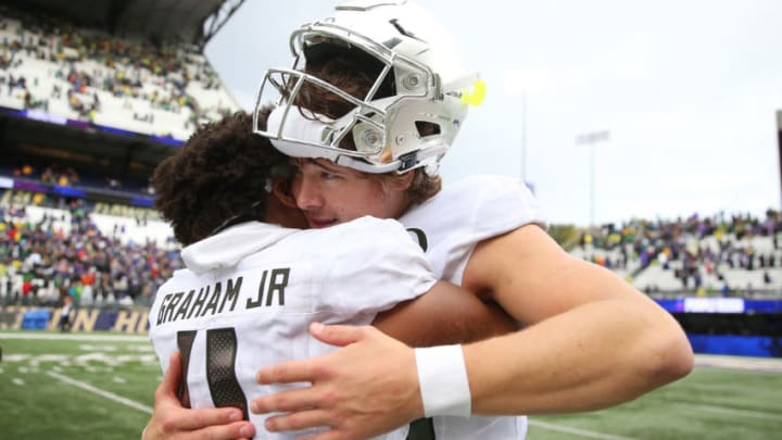 SEATTLE, WASHINGTON - OCTOBER 19: Thomas Graham Jr. #4 celebrates with Justin Herbert #10 of the Oregon Ducks after defeating the Washington Huskies 35-31 during their game at Husky Stadium on October 19, 2019 in Seattle, Washington. (Photo by Abbie Parr/Getty Images)