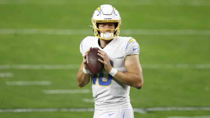 LAS VEGAS, NEVADA - DECEMBER 17: Quarterback Justin Herbert #10 of the Los Angeles Chargers holds the ball during warmups before the game against the Los Vegas Raiders at Allegiant Stadium on December 17, 2020 in Las Vegas, Nevada. (Photo by Christian Petersen/Getty Images)