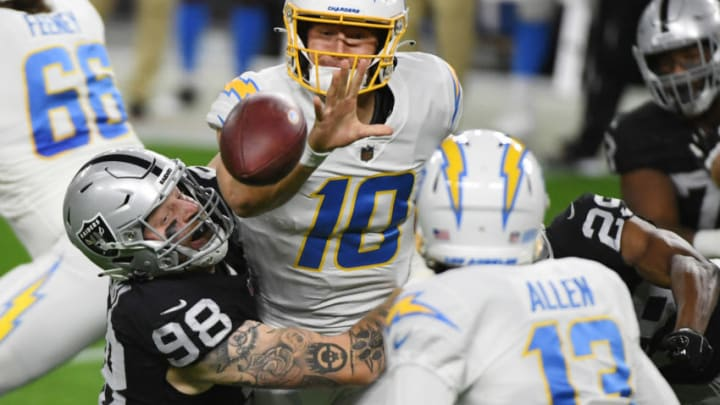LAS VEGAS, NEVADA - DECEMBER 17: Quarterback Justin Herbert #10 of the Los Angeles Chargers pitches the ball to avoid a sack from defensive end Maxx Crosby #98 of the Las Vegas Raiders during the first half at Allegiant Stadium on December 17, 2020 in Las Vegas, Nevada. (Photo by Ethan Miller/Getty Images)