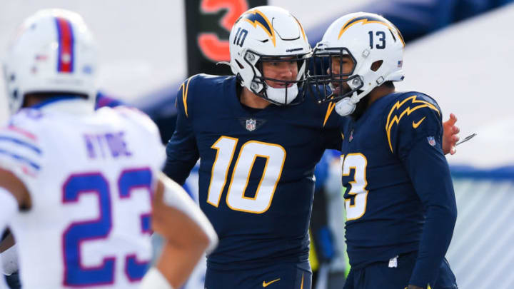 Nov 29, 2020; Orchard Park, New York, USA; Los Angeles Chargers quarterback Justin Herbert (10) celebrates after throwing a touchdown pass to wide receiver Keenan Allen (13) against the Buffalo Bills during the first quarter at Bills Stadium. Mandatory Credit: Rich Barnes-USA TODAY Sports