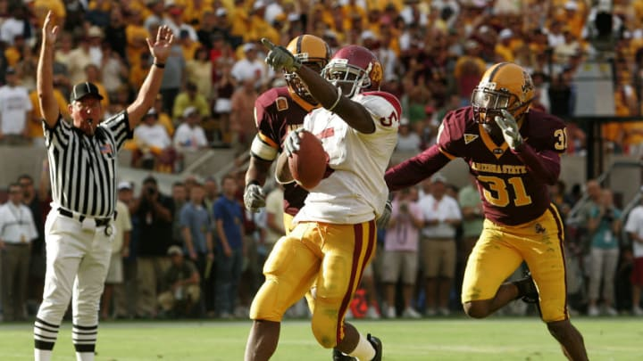 USC tailback Reggie Bush scores the go ahead touchdown late in the fourth qauter as Arizona States Josh Barrett, left, and Mike Davis Jr. give chase at Sun Devil Stadium Saturday in Tempe, Arizona. (Photo by Wally Skalij/Los Angeles Times via Getty Images)