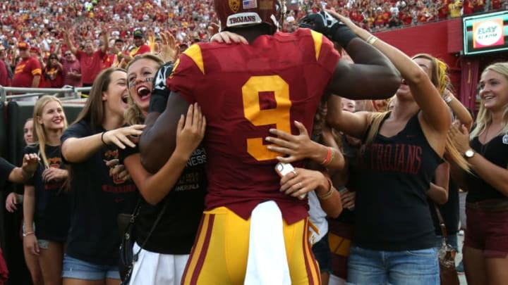 LOS ANGELES, CA - SEPTEMBER 12: Wide receiver JuJu Smith-Schuster #9 of the USC Trojans is mobbed by a group of students behind the end zone after scoring on a 50 yard touchdown pass play in tthe first quarter against the Idaho Vandals at Los Angeles Memorial Coliseum on September 12, 2015 in Los Angeles, California. (Photo by Stephen Dunn/Getty Images)