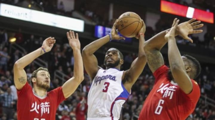 Feb 25, 2015; Houston, TX, USA; Los Angeles Clippers guard Chris Paul (3) attempts to score during the fourth quarter as Houston Rockets forward Donatas Motiejunas (20) and forward Terrence Jones (6) defend at Toyota Center. The Rockets defeated the Clippers 110-105. Mandatory Credit: Troy Taormina-USA TODAY Sports