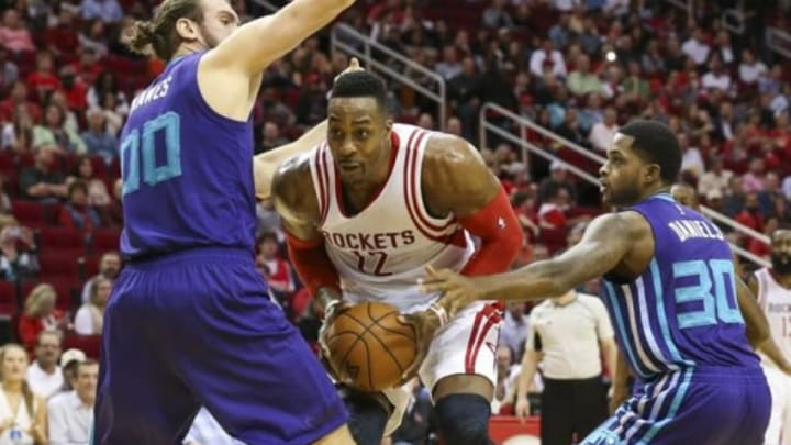 Dec 21, 2015; Houston, TX, USA; Houston Rockets center Dwight Howard (12) prepares to shoot the ball between Charlotte Hornets forward Spencer Hawes (00) and guard Troy Daniels (30) during the second quarter at Toyota Center. Mandatory Credit: Troy Taormina-USA TODAY Sports