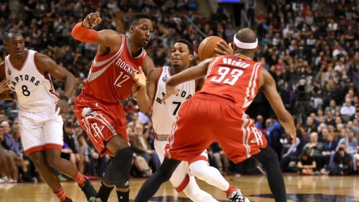 Mar 6, 2016; Toronto, Ontario, CAN; Toronto Raptors guard Kyle Lowry (7) tries to dribble between Houston Rockets center Dwight Howard (12) and forward Corey Brewer (33) in the fourth quarter at Air Canada Centre. The Rockets won 113-107. Mandatory Credit: Dan Hamilton-USA TODAY Sports