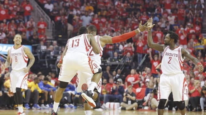 Apr 24, 2016; Houston, TX, USA; Houston Rockets guard James Harden (13) jumps on center Dwight Howard (12) as he high fives guard Patrick Beverley (2) to celebrate a play against the the Golden State Warriors in the second quarter in game four of the first round of the NBA Playoffs at Toyota Center. Mandatory Credit: Thomas B. Shea-USA TODAY Sports
