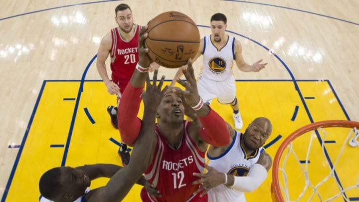 April 16, 2016; Oakland, CA, USA; Houston Rockets center Dwight Howard (12) shoots the basketball defended by Golden State Warriors forward Draymond Green (23) and center Marreese Speights (5) during the second half in game one of the first round of the NBA Playoffs at Oracle Arena. The Warriors defeated the Rockets 104-78. Mandatory Credit: Kyle Terada-USA TODAY Sports