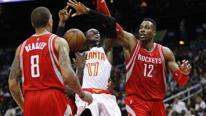Mar 19, 2016; Atlanta, GA, USA; Atlanta Hawks guard Dennis Schroder (17) is defended by Houston Rockets forward Michael Beasley (8) and center Dwight Howard (12) in the fourth quarter at Philips Arena. The Hawks defeated the Rockets 109-97. Mandatory Credit: Brett Davis-USA TODAY Sports