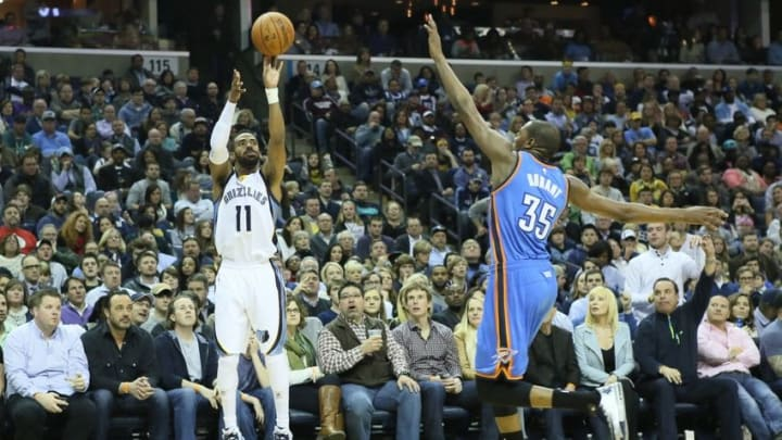 Jan 31, 2015; Memphis, TN, USA; Memphis Grizzlies guard Mike Conley (11) attempts a shot during the second quarter defended by Oklahoma City Thunder forward Kevin Durant (35) at FedExForum. Mandatory Credit: Nelson Chenault-USA TODAY Sports