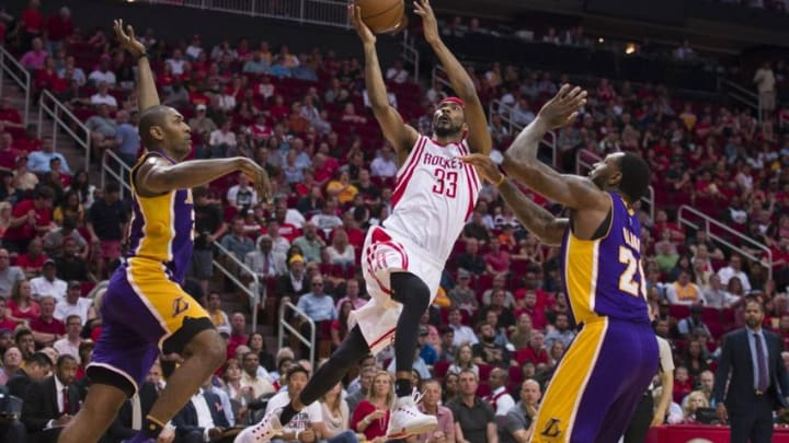 Apr 10, 2016; Houston, TX, USA; Houston Rockets guard Corey Brewer (33) shoots between Los Angeles Lakers forward Metta World Peace (37) and center Tarik Black (28) during the first half at the Toyota Center. Mandatory Credit: Jerome Miron-USA TODAY Sports