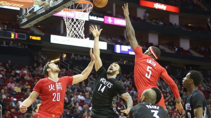 Feb 23, 2015; Houston, TX, USA; Minnesota Timberwolves center Nikola Pekovic (14) shoots against Houston Rockets forward Donatas Motiejunas (20) and forward Josh Smith (5) in the second half at Toyota Center. Rockets won 113 to 102. Mandatory Credit: Thomas B. Shea-USA TODAY Sports