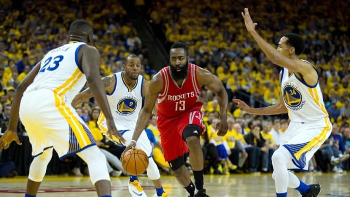 Apr 27, 2016; Oakland, CA, USA; Houston Rockets guard James Harden (13) drives in against Golden State Warriors forward Draymond Green (23), forward Andre Iguodala (9) and guard Shaun Livingston (34) during the second quarter in game five of the first round of the NBA Playoffs at Oracle Arena. Mandatory Credit: Kelley L Cox-USA TODAY Sports