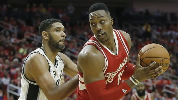 Dec 25, 2015; Houston, TX, USA; Houston Rockets center Dwight Howard (12) protects the ball from San Antonio Spurs center Tim Duncan (21) in the second half of a NBA basketball game on Christmas at Toyota Center. Rockets won 88 to 84. Mandatory Credit: Thomas B. Shea-USA TODAY Sports