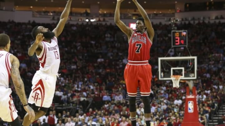 Mar 31, 2016; Houston, TX, USA; Chicago Bulls guard Justin Holiday (7) shoots the ball as Houston Rockets guard James Harden (13) defends during the fourth quarter at Toyota Center. Mandatory Credit: Troy Taormina-USA TODAY Sports