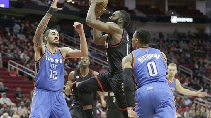 Jan 5, 2017; Houston, TX, USA; Houston Rockets guard James Harden (13) splits the defense of Oklahoma City Thunder center Steven Adams (12) and guard Russell Westbrook (0) in the first quarter at Toyota Center. Mandatory Credit: Thomas B. Shea-USA TODAY Sports