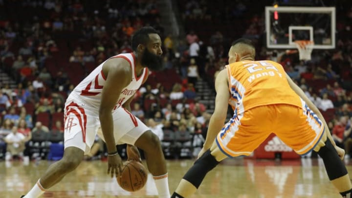 James Harden #13 of the Houston Rockets controls the ball defended by Wang Tong #25 of the Shanghai Sharks (Photo by Tim Warner/Getty Images)