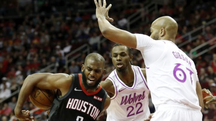 HOUSTON, TX - MARCH 17: Chris Paul #3 of the Houston Rockets looses control of the ball defended by Andrew Wiggins #22 of the Minnesota Timberwolves and Taj Gibson #67 in the first half at Toyota Center on March 17, 2019 in Houston, Texas. NOTE TO USER: User expressly acknowledges and agrees that, by downloading and or using this photograph, User is consenting to the terms and conditions of the Getty Images License Agreement. (Photo by Tim Warner/Getty Images)