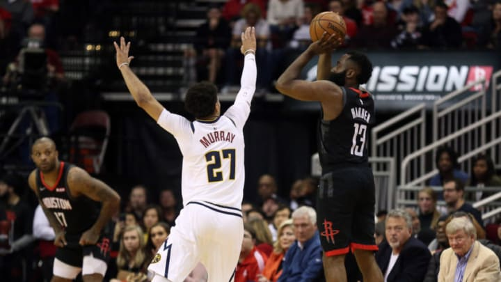 HOUSTON, TEXAS - DECEMBER 31: James Harden #13 of the Houston Rockets shoots a three point basket over Jamal Murray #27 of the Denver Nuggets during the fourth quarter at Toyota Center on December 31, 2019 in Houston, Texas. NOTE TO USER: User expressly acknowledges and agrees that, by downloading and/or using this photograph, user is consenting to the terms and conditions of the Getty Images License Agreement. (Photo by Bob Levey/Getty Images)
